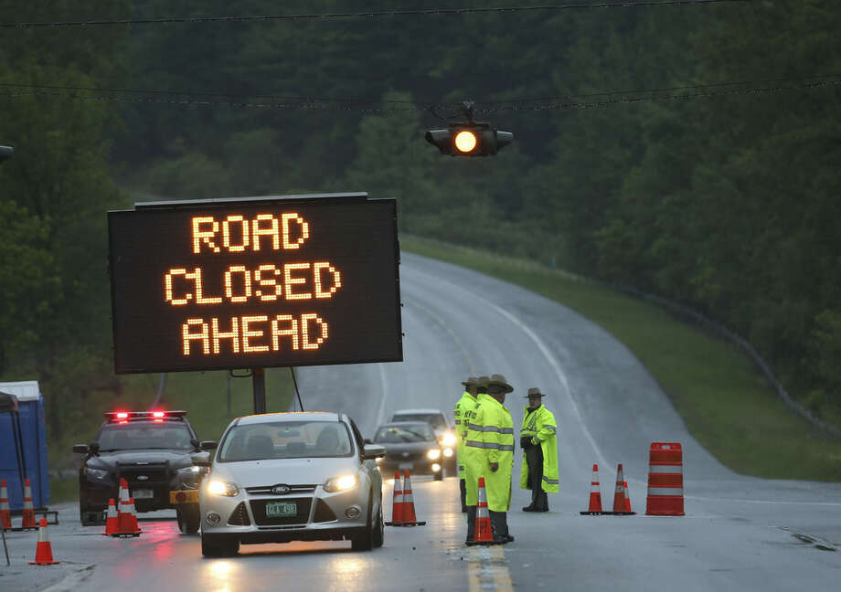State Police man a road block on Route 374 on Monday, June 15, 2015, in West Plattsburgh, N.Y. Law enforcement personnel are in the tenth day of searching for David Sweat and Richard Matt, two killers who used power tools to cut their way out Clinton Correctional Facility in Dannemora in northern New York. (AP Photo/Mike Groll)