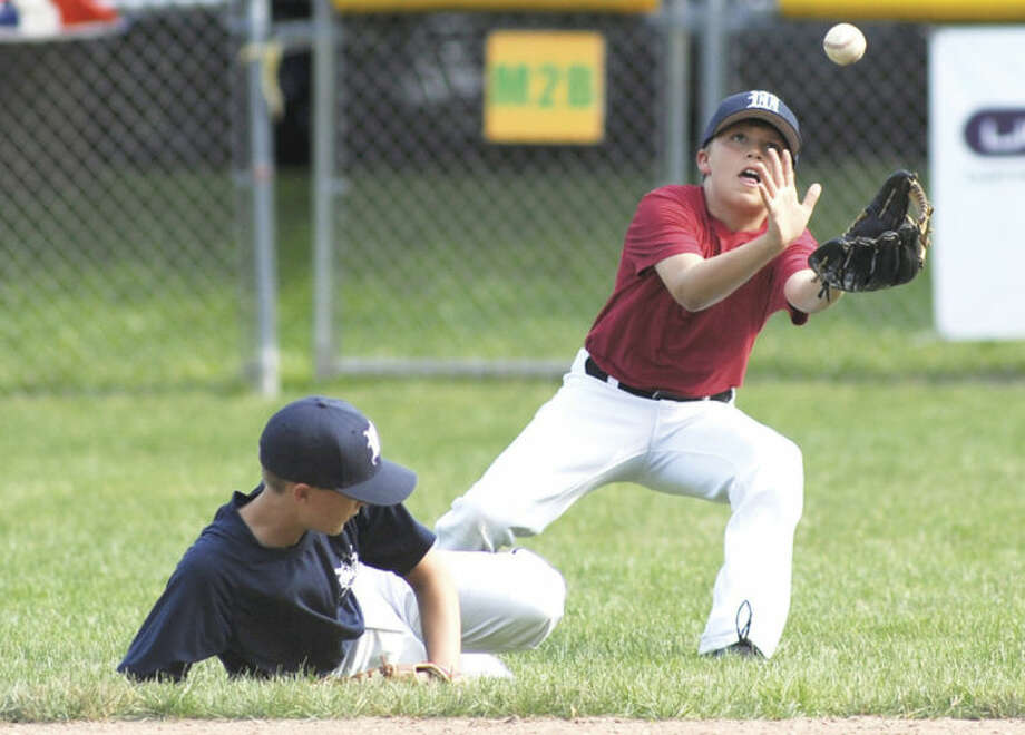 Hour photo/John NashKyle Hyzy, center fielder for the Wilton Little League All-Stars, keeps his focus on catching the ball as teammate Drew Phillips avoids a collision during a practice Monday at Bill Terry Field in Wilton.