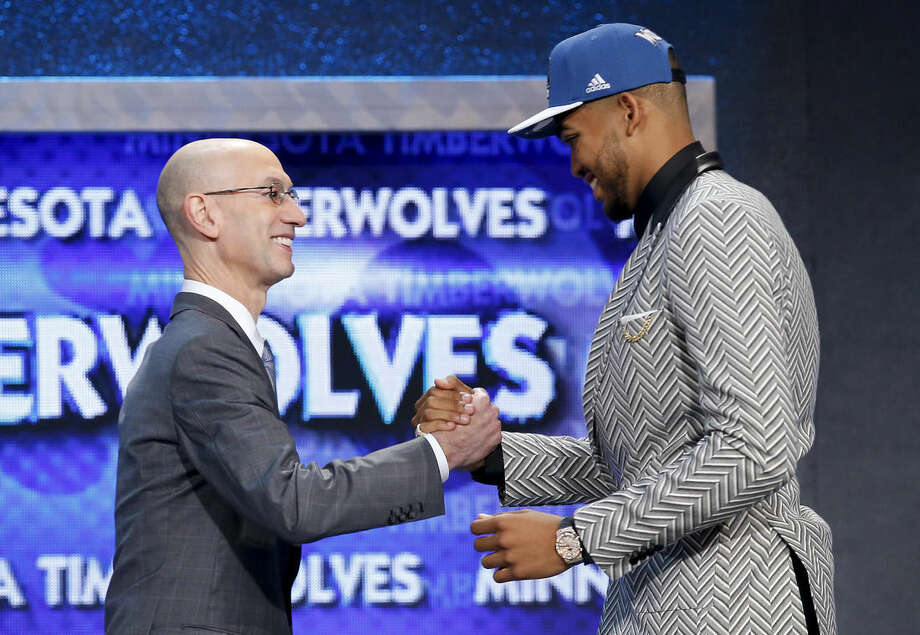 Karl-Anthony Towns, right, is greeted by NBA Commissioner Adam Silver after being announced as the top pick, by the Minnesota Timberwolves, at the NBA basketball draft Thursday, June 25, 2015, in New York. (AP Photo/Kathy Willens)