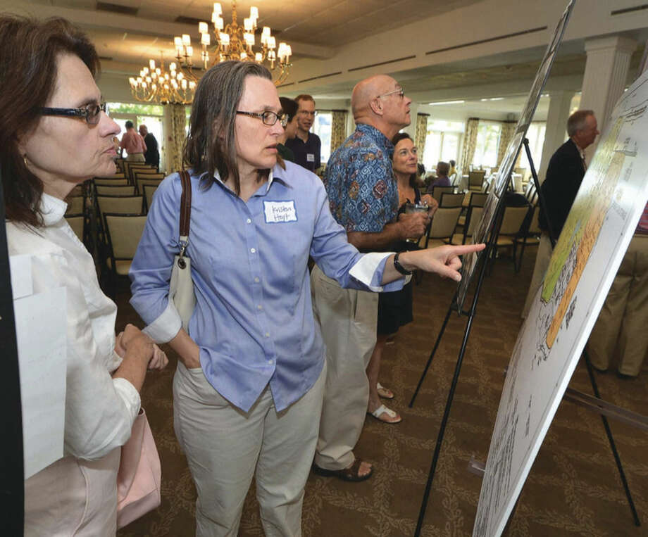 Hour photo/Alex von Kleydorff.Kristen Hoyt and Ellen Mitten look at a map of the Manresa property and the power plant during the Manresa Association meeting at Shore and Country Club Wednesday evening.
