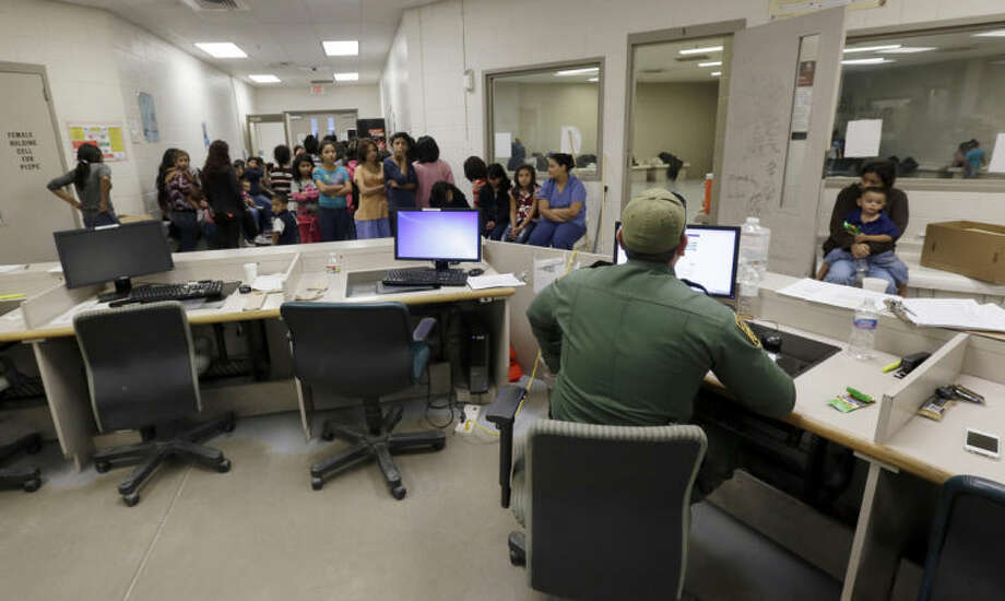 FILE - This June 18, 2014, file photo shows U.S. Customs and Border Protection agents work at a processing facility in Brownsville,Texas. Thousands of immigrant children crossing alone into the U.S. can live in American cities, attend public schools and possibly work here for years without consequences, chiefly because of an overburdened, deeply flawed system of immigration courts, and a 2002 law intended to protect children's welfare, an Associated Press investigation finds. The Obama administration estimates it will catch 90,000 children trying to illegally cross the Mexican border without their parents by the end of the current budget year in September. Fewer than 2,000 children were returned to their native countries last year. (AP Photo/Eric Gay, Pool)