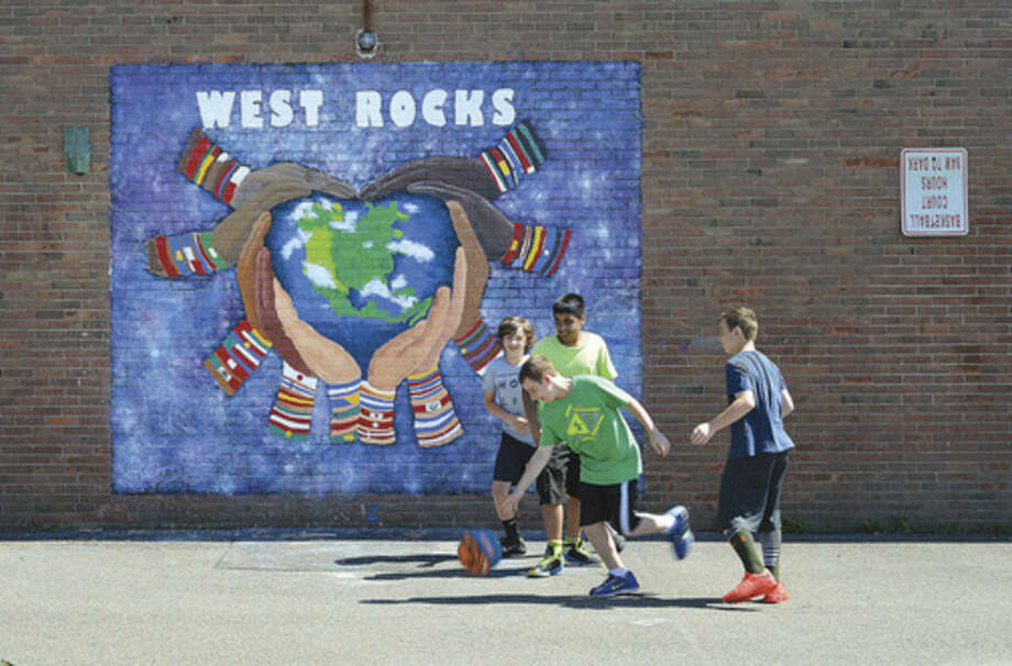 Hour photo/Alex von KleydorffWest Rocks Middle School recently unveiled its first outdoor mural. Recent graduates that participated in the school's Artistically Talented program painted the mural as a parting gift to the school. It is located at the back of the school on West Rocks Road, and faces Aiken Street. This past school year, West Rocks Middle School promoted empathy and non-violence among students. The painting project, which was led by art teacher Melissa Fusarelli, shows a number of hands, surrounding the Earth and reshaping the planet into a heart. In the past, graduating eighth graders have painted indoor murals that decorate the school's halls.