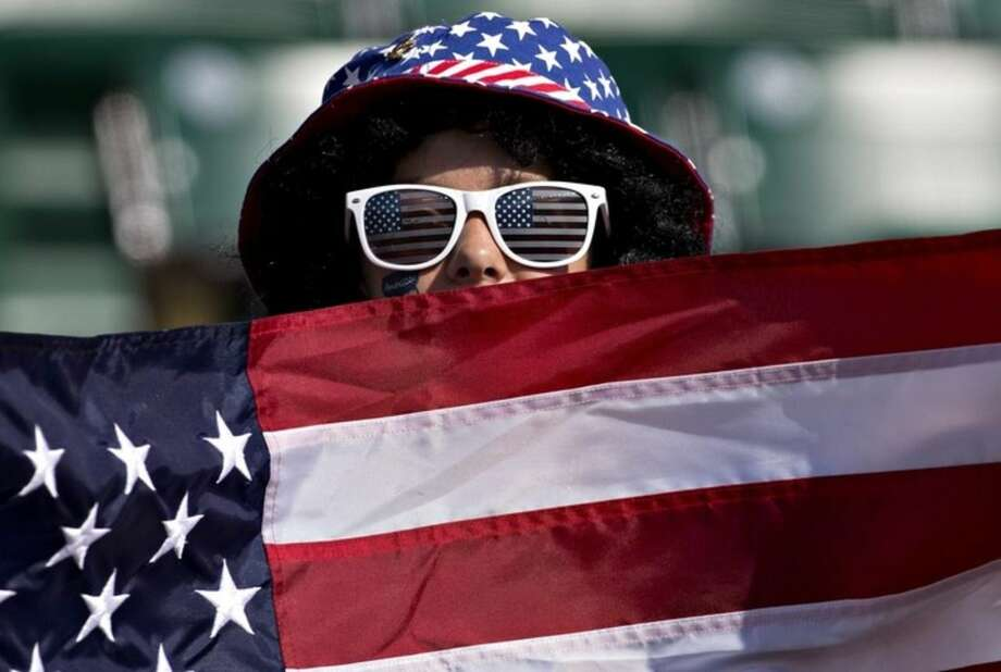 A United States fan holds up a U.S. flag before the FIFA Women's World Cup round of 16 action against Colombia in Edmonton, Alberta, Canada, Monday, June 22, 2015. (Jason Franson/The Canadian Press via AP) MANDATORY CREDIT