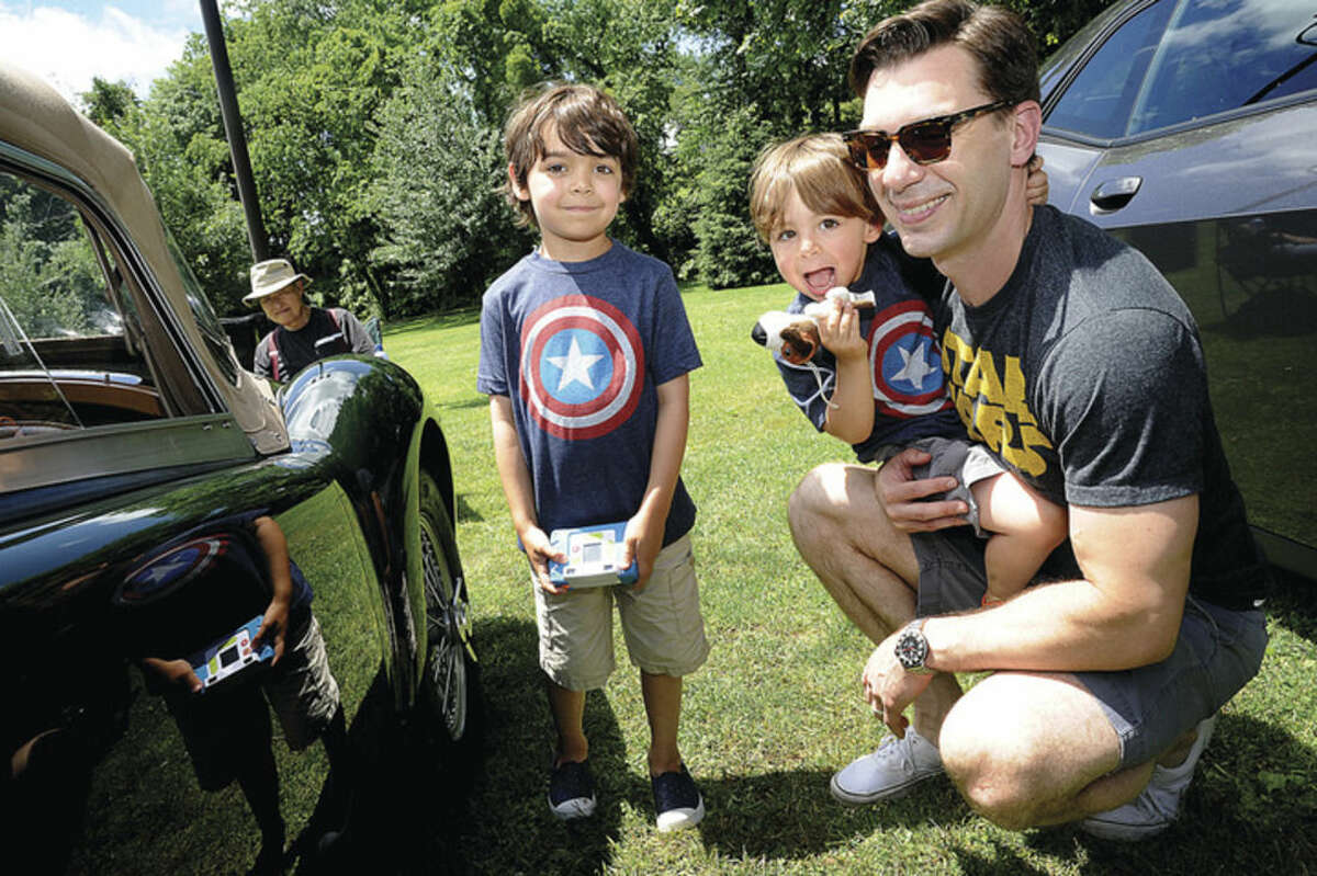 Hour photo/Matthew Vinci Jon Hammond with his sons Ben 6 and Dylan 2 enjoy the New England Auto Museum's Father's Day car show Sunday at Mathews Park.