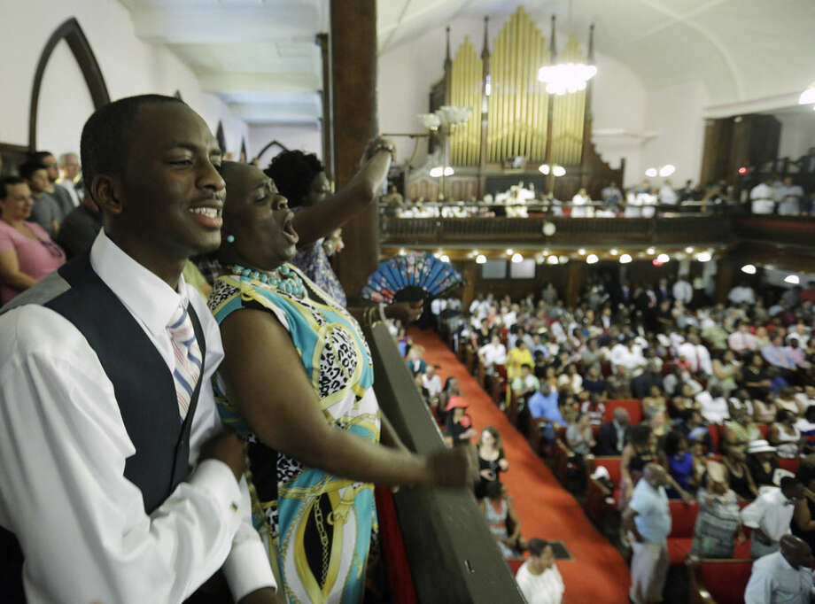 Parishioners Shakur Francis, left, and Karen Watson-Fleming sing at the Emanuel A.M.E. Church Sunday, June 21, 2015, in Charleston, S.C., four days after a mass shooting that claimed the lives of it's pastor and eight others. (AP Photo/David Goldman, Pool)