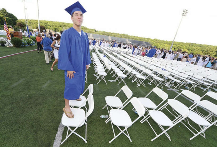 Hour photo / Erik Trautmann Wilton High School graduate Andrew Sakamoto looks for relatives following the Class of 2014 commencement exercises Saturday.