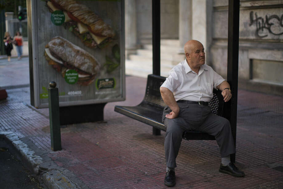 A man waits for public transportation sitting at a bus station in central Athens, Wednesday, July 8, 2015. Frustrated and angry eurozone leaders fearing for the future of their common currency gave the Greek Prime Minister Alexis Tsipras a last-minute chance Tuesday to finally come up with a viable proposal on how to save his country from financial ruin. (AP Photo/Emilio Morenatti)