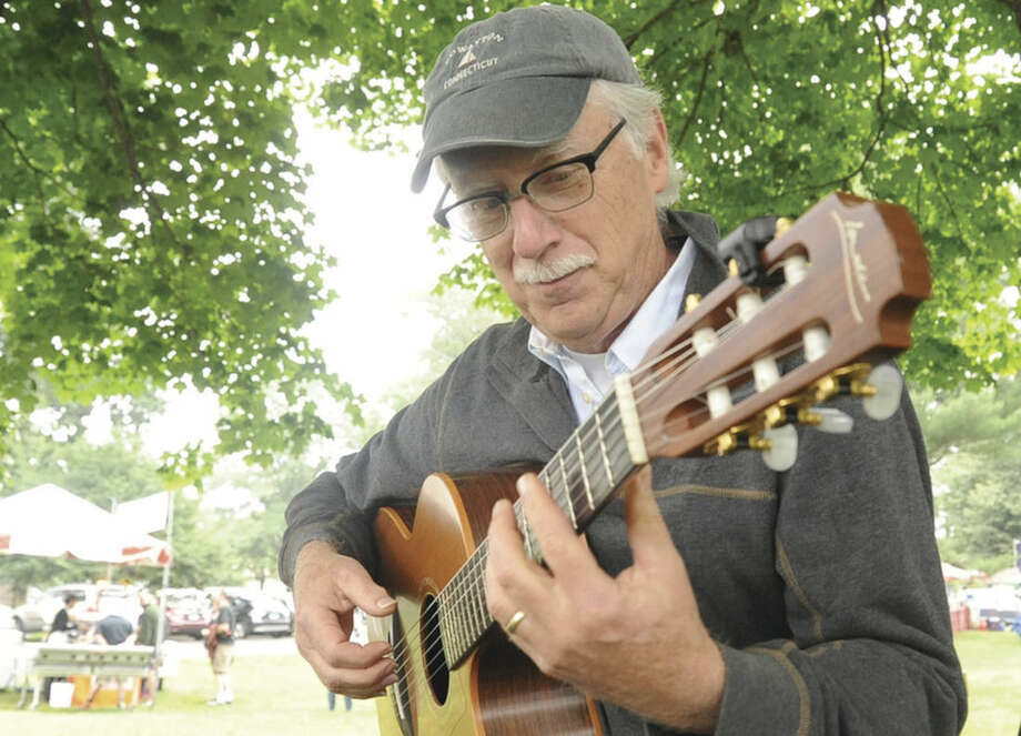 Musican Edward Wright performs songs on his acoustic guitar with cds for sale on Sunday at the Norwalk Arts Festival. Hour photo/Matthew Vinci