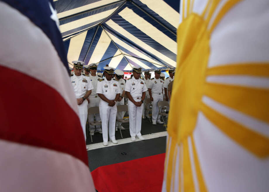 U.S. and Philippine Navy officers stand for an invocation during the opening of the 20th Cooperation Afloat Readiness And Training (CARAT) joint U.S.-Philippines naval exercise at the former U.S. naval base of Subic, about 70 miles west of Manila, Philippines Thursday, June 26, 2014. After more than a decade of helping fight al-Qaida-linked militants, the United States is disbanding an anti-terror contingent of hundreds of elite American troops in the southern Philippines where armed groups such as the Abu Sayyaf have largely been crippled, officials said Thursday. The move reflects shifting security strategies and focus in economically vibrant Asia, where new concerns such as multiple territorial conflicts involving China have alarmed Washington's allies entangled in the disputes. (AP Photo/Bullit Marquez)