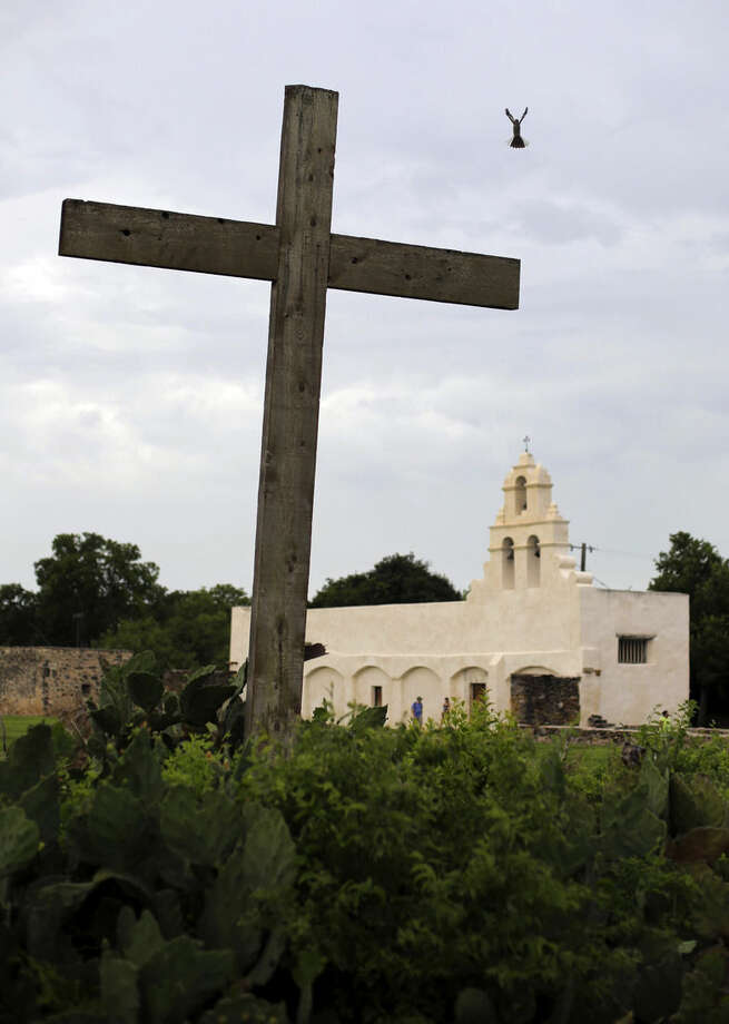 FILE - In this June 30, 2015 file picture a bird takes flight from a cross at Mission San Juan, in San Antonio,Texas, USA . The San Antonio Missions in Texas have been awarded world heritage status by the U.N.'s cultural body. UNESCO's World Heritage Committee approved the listing Sunday July 5, 2015 of the five Spanish Roman Catholic sites built in the 18th century in an around what is now the city of San Antonio. he missions were the only site in the United States proposed for world heritage status at this year's UNESCO meeting in Bonn, Germany. (AP Photo/Eric Gay,File)