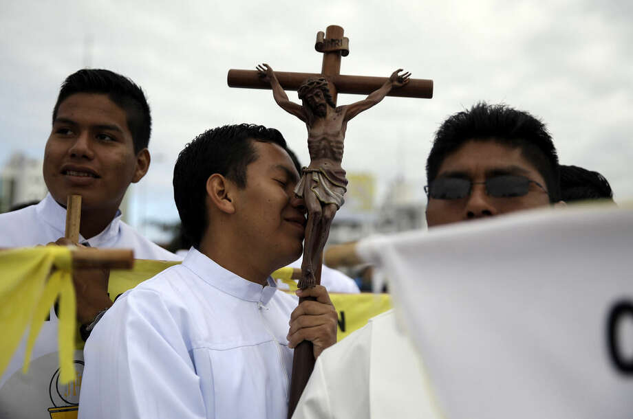 Seminarian Carmelo Tubari Gutierrez kisses a crucifix as he waits with other seminarians for the arrival of Pope Francis, at Christ the Redeemer square in Santa Cruz, Bolivia, Thursday, July 9, 2015. Hundreds of thousands packed the square and the streets beyond. Overnight, several thousand slept in square to get a spot close to the front. Francis arrived in the Andean nation late Wednesday after three days in Ecuador. (AP Photo/Gregorio Borgia)
