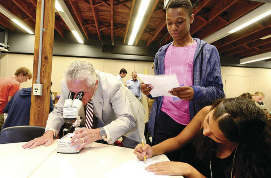"""Hour photo / Erik Trautmann Norwalk Mayor Harry Rilling looks through a microscope as 8th and 9th graders including Luca Napoli-Bulteryst and Kiana Rodriguez participate in the """"Marine World Magnified"""" activity, using microscopes to observe small marine organisms, as part of the Mayor's Student Engineering & Science Program Thursday at the Maritime Aquarium. The Mayor's Student Engineering & Science Program is a new initiative funded by city residents' participation in the Norwalk Energy Efficiency Challenge."""