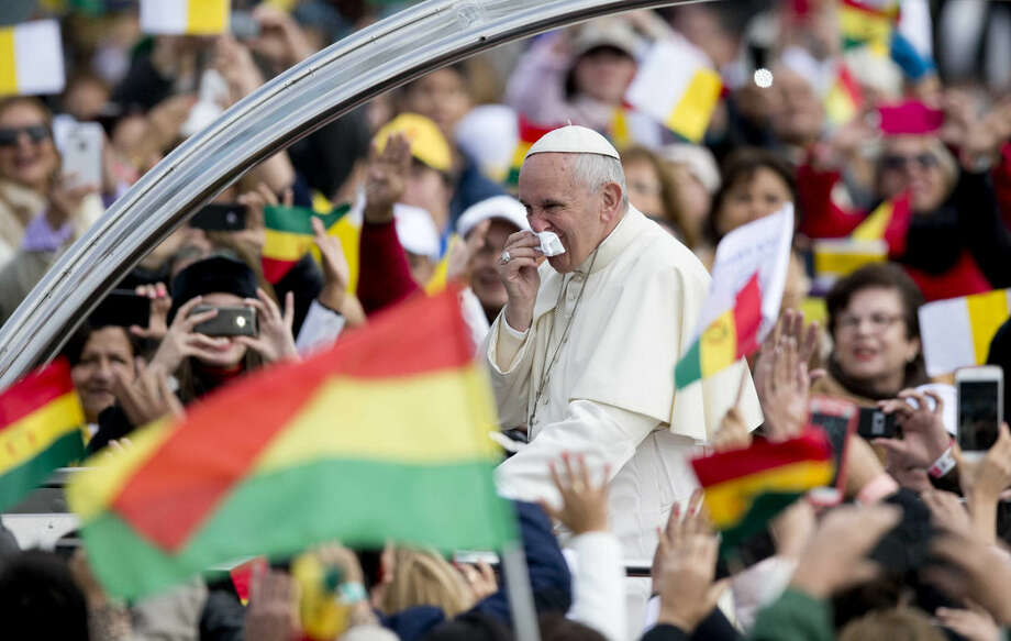 Pope Francis wipes his nose as he arrives in his popemobile to celebrate Mass at the Christ the Redeemer square in Santa Cruz, Bolivia, Thursday, July 9, 2015. Francis rallied tens of thousands of flag-waving Bolivians during his first public Mass in Bolivia on Thursday, one of the key days of his South American pilgrimage. (AP Photo/Eduardo Verdugo)