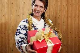 Man with mullet in big Christmas jumper presenting big present