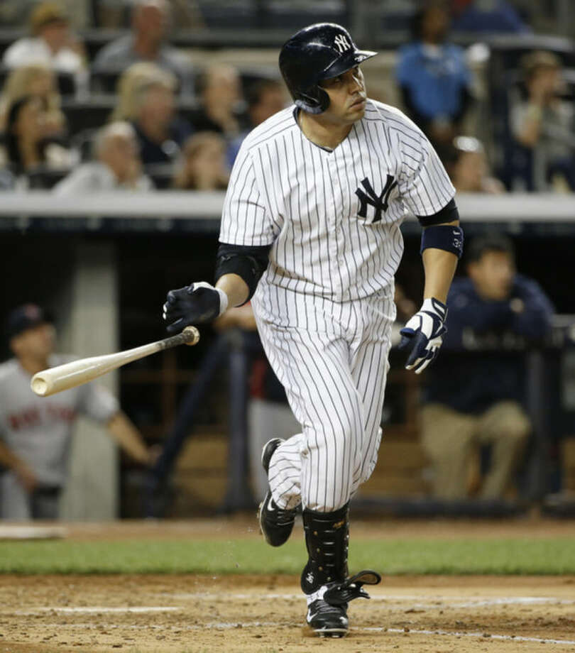 New York Yankees designated hitter Carlos Beltran tosses his bat after hitting a fourth-inning, solo home run off Boston Red Sox starting pitcher John Lackey in a baseball game at Yankee Stadium in New York, Sunday, June 29, 2014. (AP Photo/Kathy Willens)
