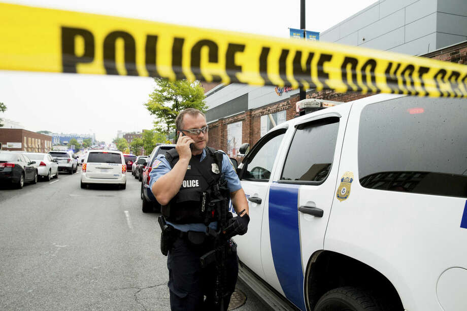 A police officer speaks on his phone as a large police presence gathers along M St. in Southeast Washington, Thursday, July 2, 2015, after an official said shots have been reported in a building on the Washington Navy Yard campus. (AP Photo/Andrew Harnik)