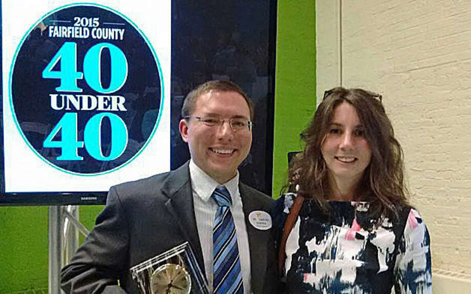 "Contributed photoBruce Museum Curator of Science Daniel Ksepka poses with his exhibit ""Madagascar: Ghosts of the Past."" Ksepka received Fairfield County Business Journal's ""40 Under 40"" award in a ceremony last week at the Maritime Aquarium."