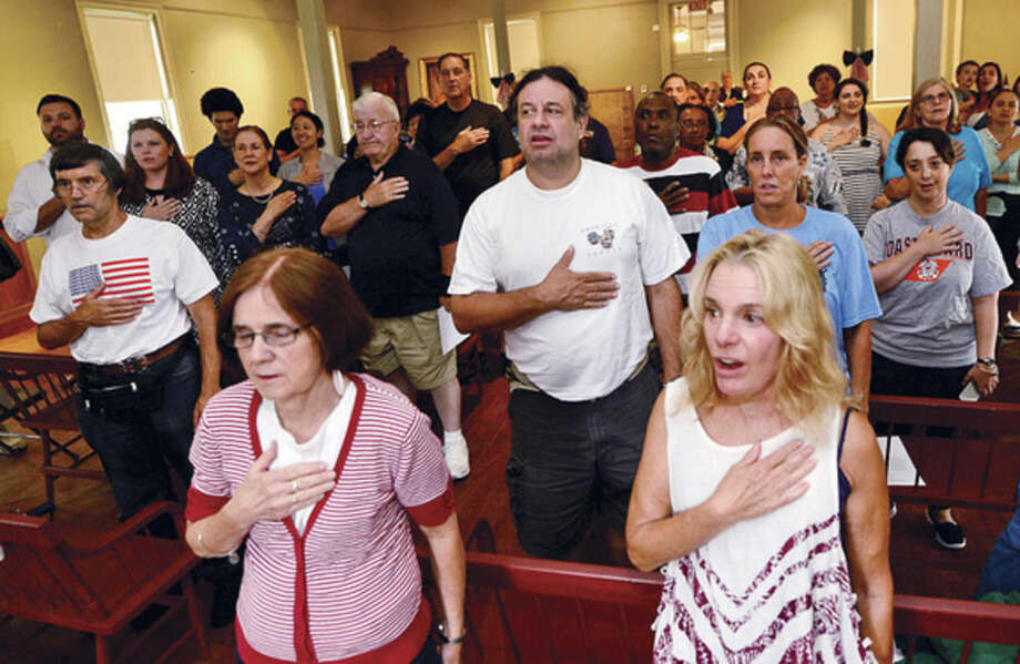 """Claudia Parra, lower right, joins other Norwalk residents reciting the Pledge of Allegiance during the Norwalk Historical Society's Independence Day """"Let Freedom Ring"""" National Bell Ringing Ceremony Saturday at the Mill Hill Historic Complex."""