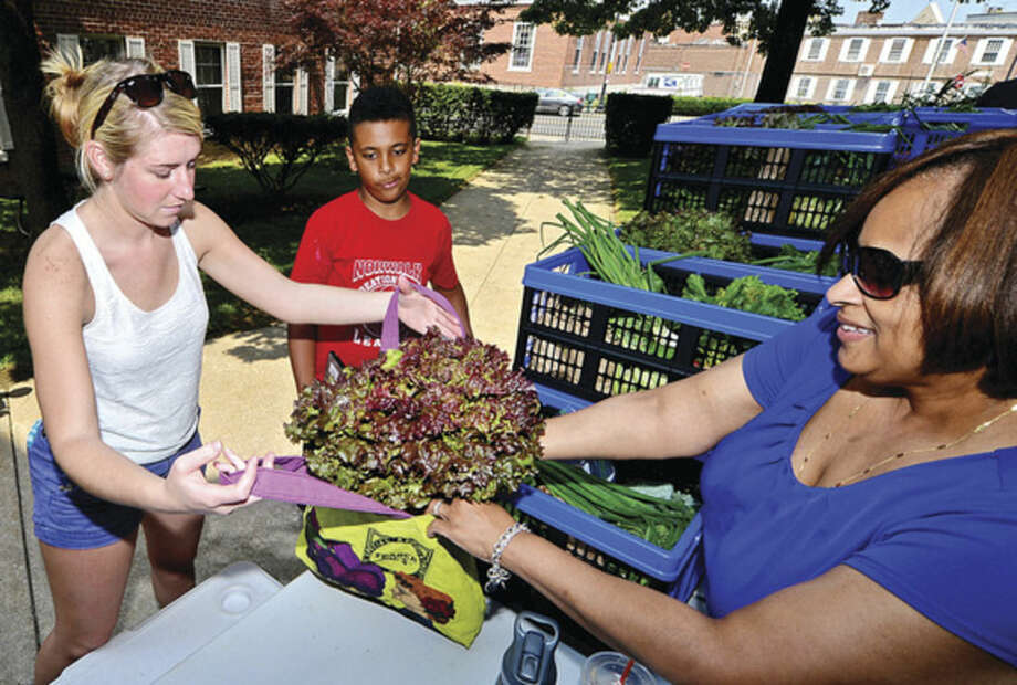 Hour photo/Erik TrautmannCustomers of the library's new CSA program, Kaitlyn Fitzpatrick and Andrew Fieffe, 10, pick up farm-fresh produce from Children's Circulation Supervisor, Laurie James, at the library Wednesday.