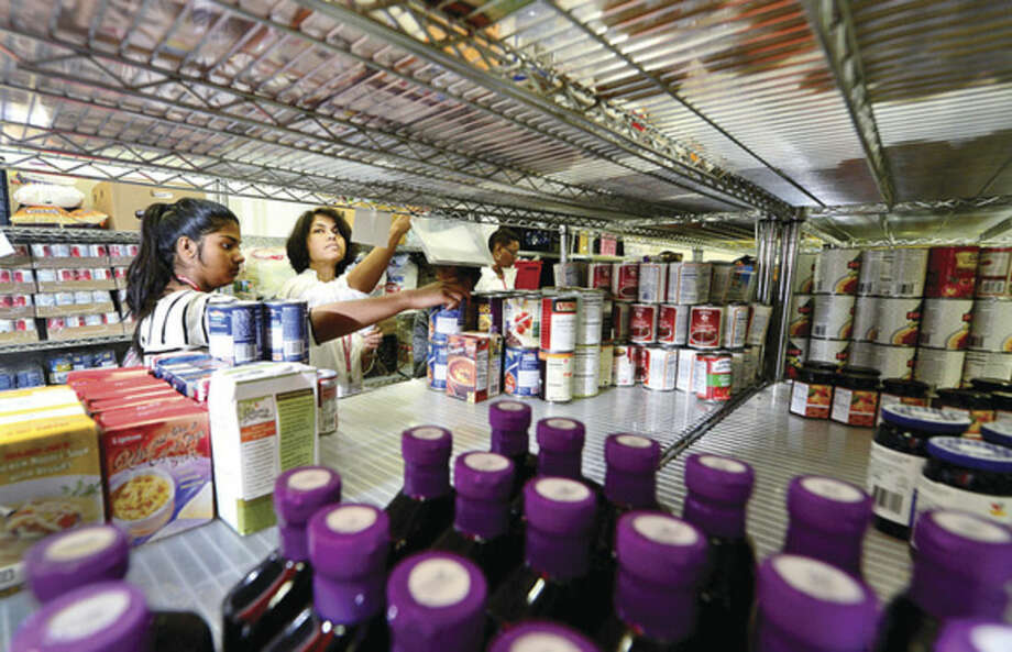 Hour photo / Erik TrautmannPerson to Person volunteers Chawa Dagli, right, and her daughter, Kavya, 13, stock shelves Thursday afternoon in Norwalk. Person to Person is seeking food donations as summer donations fall off and need tends to rise.
