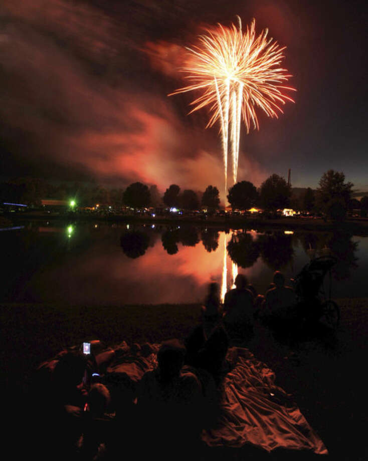 People watch a fireworks display to commemorate the Independence Day holiday, Thursday night, July 3, 2014, in Owensboro, Ky. (AP Photo/The Messenger-Inquirer, John Dunham)
