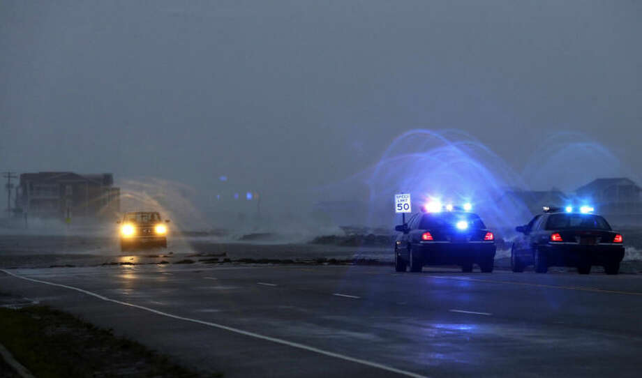 Police watch a flooded area as a vehicle navigates Highway 64 as wind pushes water over the road while Hurricane Arthur passes through Nags Head, N.C., Friday, July 4, 2014. (AP Photo/Gerry Broome)