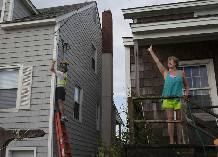 Missy McGraw, right, of Richmond, Va., waves to a neighbor as her husband, Art, works to repair a cable line on a neighbor's beach house in Atlantic Beach, N.C., Friday, July 4, 2014. Damage was scattered and light along the North Carolina coast near where the eye of Hurricane Arthur came ashore on Thursday evening. (AP Photo/Randall Hill)