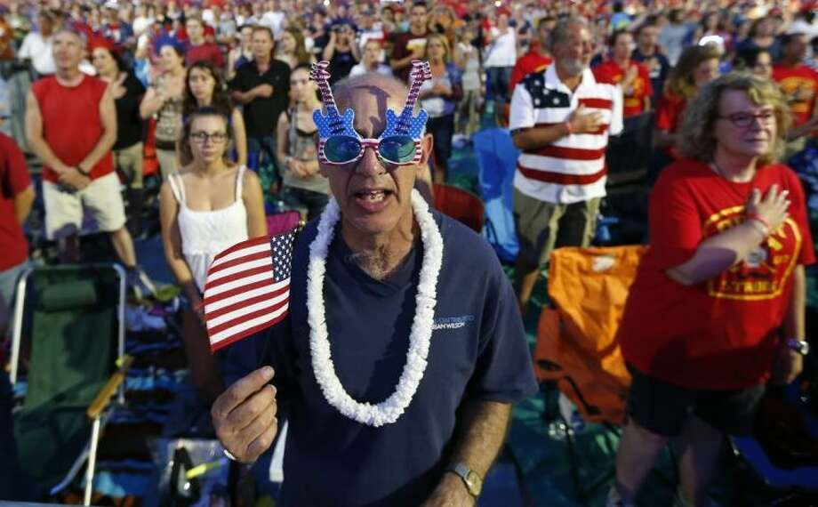 Doc Rutstein, of Braintree, Mass., sings along to the national anthem during a concert at the Hatch Shell on the Esplanade in Boston, Thursday, July 3, 2014. The annual Boston Pops Fourth of July concert was moved up a day because of potential heavy rain ahead of Hurricane Arthur. (AP Photo/Michael Dwyer)