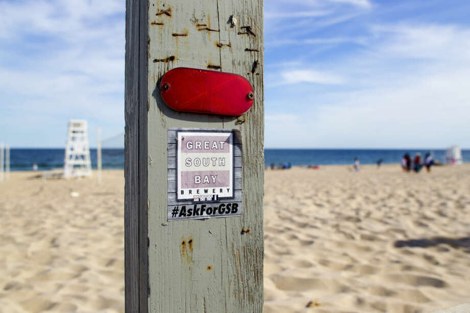 HOLD FOR STORY BY MICHAEL SISAK - This June 23, 2014 photo shows a sticker advertising a local brewery on a post at Indian Wells Beach, in Amagansett, N.Y., where the East Hampton Town Board is proposing banning alcohol after complaints about out of towners getting drunk and rowdy last year. The town trustees, an elected body that controls most of the town's beaches and dates to colonial times, are objecting to the plan. (AP Photo/Michael R. Sisak)