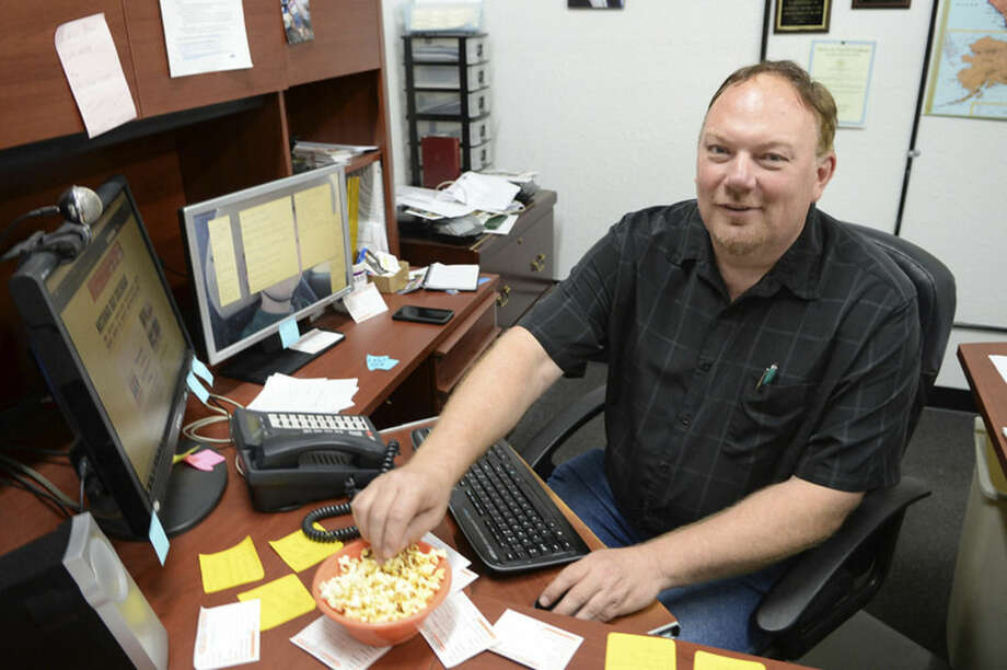 In this June 16, 2015 photo, Zoovio co-owner Marlo Anderson eats popcorn at his desk at his Mandan, N.D. business. Anderson says he started an online compendium of special days in 2013 called National Day Calendar after his love of popcorn piqued his curiosity about National Popcorn Day (Jan. 19). (AP Photo/Will Kincaid)