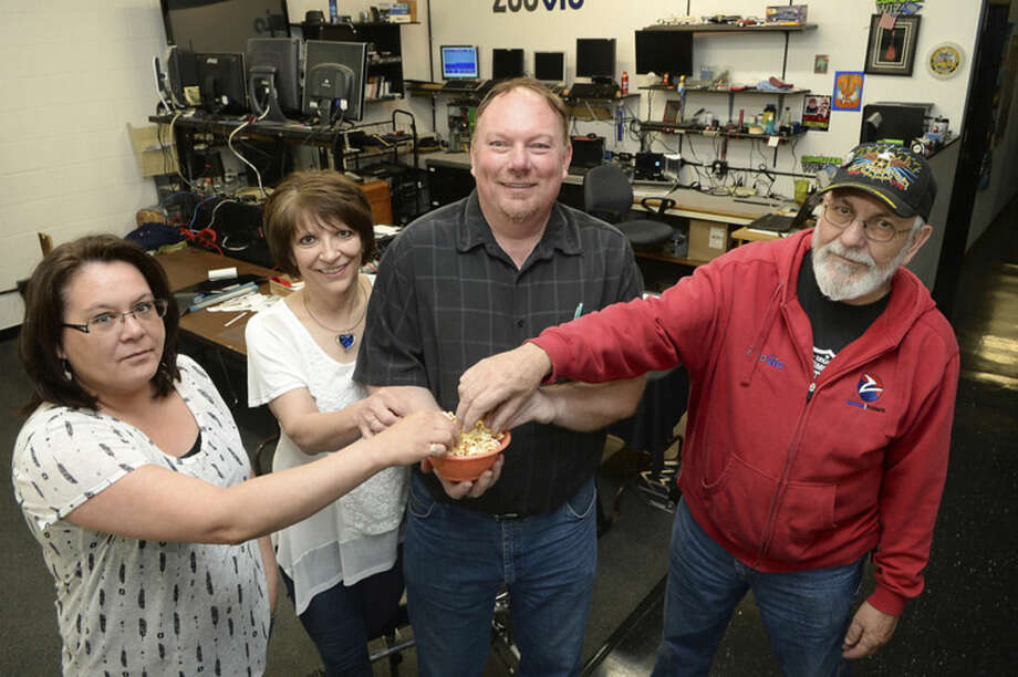 In this June 16, 2015 photo, Zoovio co-owner Marlo Anderson, center, and some of the National Day Calendar review committee, including, from left, Zoovio employees Amy LaVallie, Alice Anderson, and Nicholas Ressler, pose for a photo with a bowl of popcorn at the Mandan, N.D. business. Anderson says he started an online compendium of special days in 2013 called National Day Calendar after his love of popcorn piqued his curiosity about National Popcorn Day (Jan. 19). (AP Photo/Will Kincaid)
