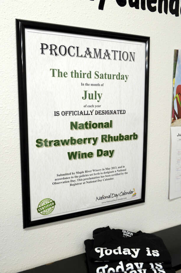 In this June 16, 2015 photo, a proclamation for National Strawberry Rhubarb Wine Day hangs on the wall at Zoovio, a business co-owned by Marlo Anderson, in Mandan, N.D. Anderson says he started an online compendium of special days in 2013 called National Day Calendar after his love of popcorn piqued his curiosity about National Popcorn Day (Jan. 19). National Strawberry Rhubarb Wine Day was Anderson's first National Day when he started the calendar in 2013. (AP Photo/Will Kincaid)