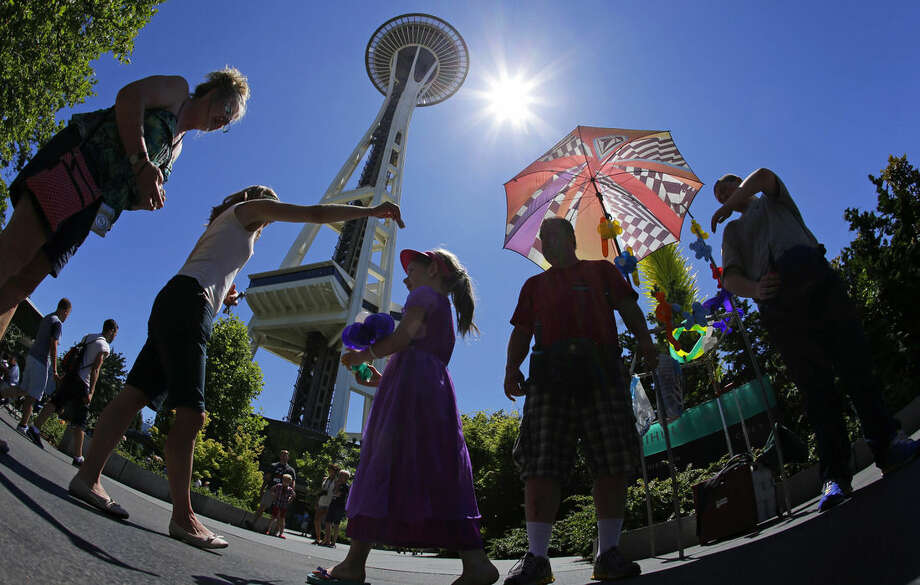 In this photo taken July 1, 2015, Kevin Pinnell, second from right, shows that people in Seattle don't just need umbrellas during the rainy season as he stands under his for shade from the sun while selling balloon creations to visitors to the Space Needle in Seattle. From Seattle to Salt Lake City, the West is baking under record heat. (AP Photo/Ted S. Warren)