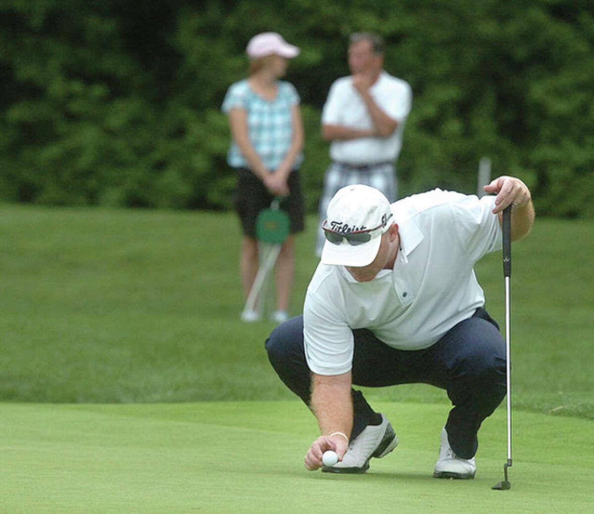 Hour photo/Alex von Kleydorff Frank Bensel of Norwalk re-places his ball while lining up a putt during the second round of the Connecticut Open at Wee Burn Country Club in Darien. The defending champ, Bensel shot 75 and is four shots off the lead.