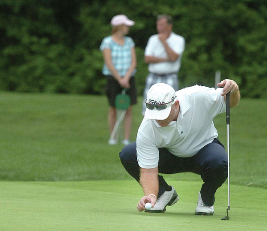 Hour photo/Alex von KleydorffFrank Bensel of Norwalk re-places his ball while lining up a putt during the second round of the Connecticut Open at Wee Burn Country Club in Darien. The defending champ, Bensel shot 75 and is four shots off the lead. / 2012 The Hour Newspapers