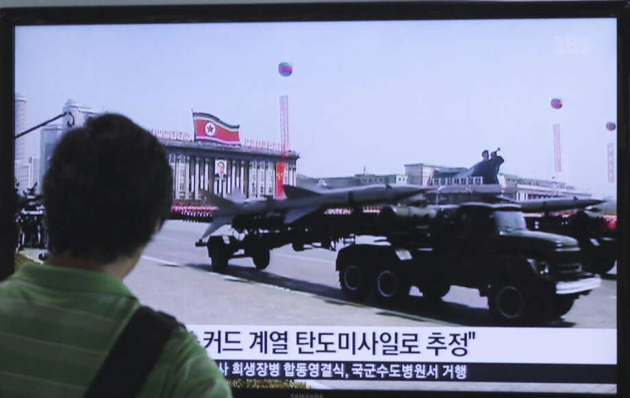 """A man watches a TV news program showing file footage of a North Korean rocket carried during a military parade at Seoul Railway Station in Seoul, South Korea, Sunday, June 29, 2014. North Korea fired two short-range missiles into its eastern waters Sunday, a South Korean official said, an apparent test fire that comes just days after the country tested what it called new precision-guided missiles. The writing on the screen reads """"North Korea fired 2 missiles presumed to be scuds."""" (AP Photo/Ahn Young-joon)"""