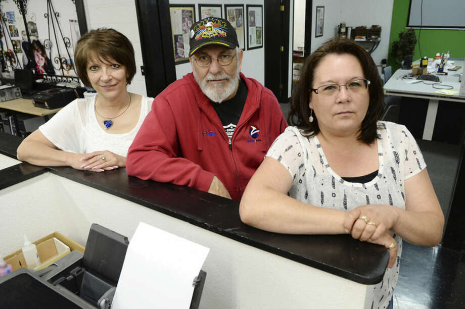 In this June 16, 2015 photo, from left, Zoovio employees Alice Anderson, Nicholas Ressler and Amy LaVallie, who serve on co-owner Marlo Anderson's National Day selection committee, pose for photos at the business in Mandan, N.D. Anderson says he started an online compendium of special days in 2013 called National Day Calendar after his love of popcorn piqued his curiosity about National Popcorn Day (Jan. 19). (AP Photo/Will Kincaid)