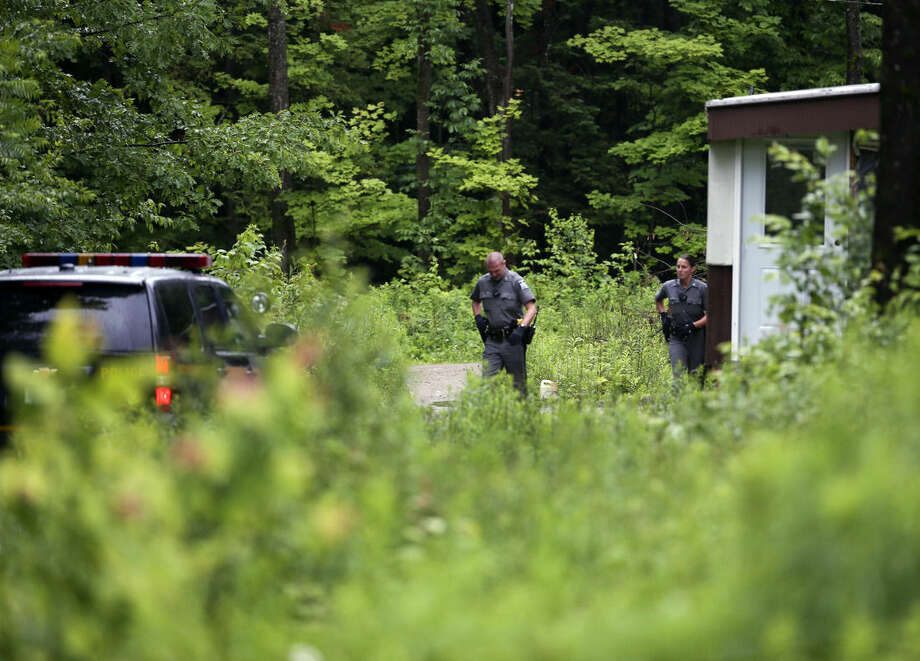New York State Police troopers search a camp on Sunday, June 28, 2015, in Malone, N.Y. The shooting death of one escaped killer brought new energy to the three-week hunt for a second escaped murderer in the United States as helicopters, search dogs and hundreds of law enforcement officers converged on a wooded area 30 miles from Clinton Correctional Facility. (AP Photo/Mike Groll)