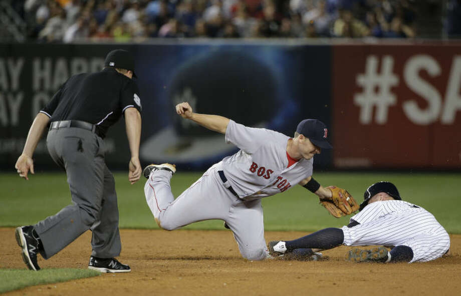New York Yankees' Brett Gardner, right, is tagged out by Boston Red Sox shortstop Stephen Drew as he attempts to steal second base in the sixth inning of a baseball game, Saturday, June 28, 2014, in New York. (AP Photo/Julie Jacobson)