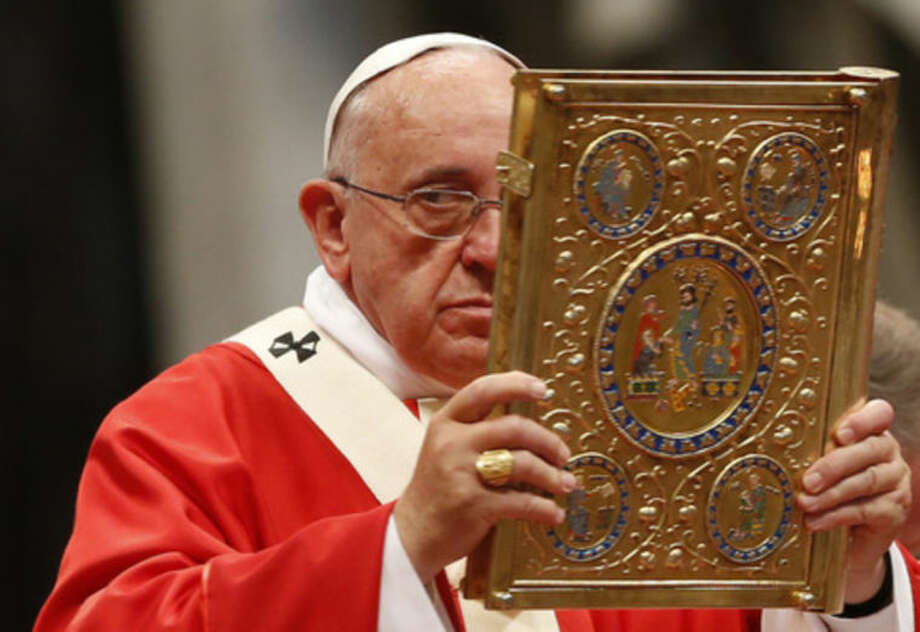 Pope Francis hoists the Gospel book during a mass where he bestowed the Pallium, a woolen shawl symbolizing their bond to the pope, to 24 new new Metropolitan Archbishops, in St. Peter's Basilica at the Vatican, Sunday, June 29, 2014. (AP Photo/Riccardo De Luca)