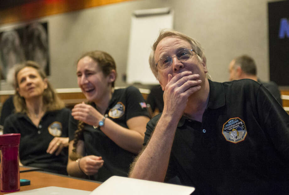 Members of the New Horizons science team reacttoseeing thespacecraft'slast and sharpestimage of Pluto before closest approach later in the day, Tuesday, July 14, 2015 at the Johns Hopkins University Applied Physics Laboratory (APL) in Laurel, Maryland. NASA's New Horizons spacecraft was on track to zoom within 7,800 miles (12,500 kilometers) of Pluto on Tuesday. (Bill Ingalls/NASA via AP)