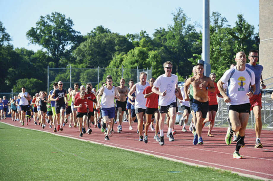 Hour photo / Erik TrautmannRunners take off from the start of the Westport Road Runners race at Staples High School Saturday.