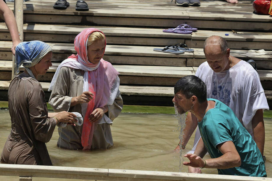 In this July 6, 2015 photo, Christian visitors immerse themselves in the Jordan River at the baptismal area of the Israeli-run site known as Qasr al-Yahud, located in a part of the West Bank, seen from the eastern bank of the river in South Shuna, Jordan. UNESCO recently designated Jordan's baptismal area a World Heritage site, over the Israeli-run site of Qasr al-Yahud in the West Bank, which is one of three territories captured by Israel in the 1967 Mideast war. (AP Photo/Raad Adayleh)