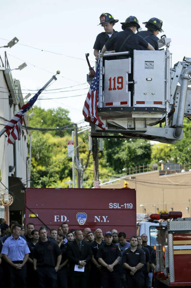 Firefighters on the ground watch as other firefighters hang bunting in honor of Lt. Gordon Ambelas in New York, Sunday, July 6, 2014. The Fire Department of New York is mourning the death of Ambelas, who became trapped while looking for victims in a public-housing high-rise blaze, the first to die in the line of duty in more than two years. Ambelas died Saturday after suffering multiple injuries while on the 19th floor of the 21-story building in the Williamsburg section of Brooklyn, officials said. (AP Photo/Seth Wenig)