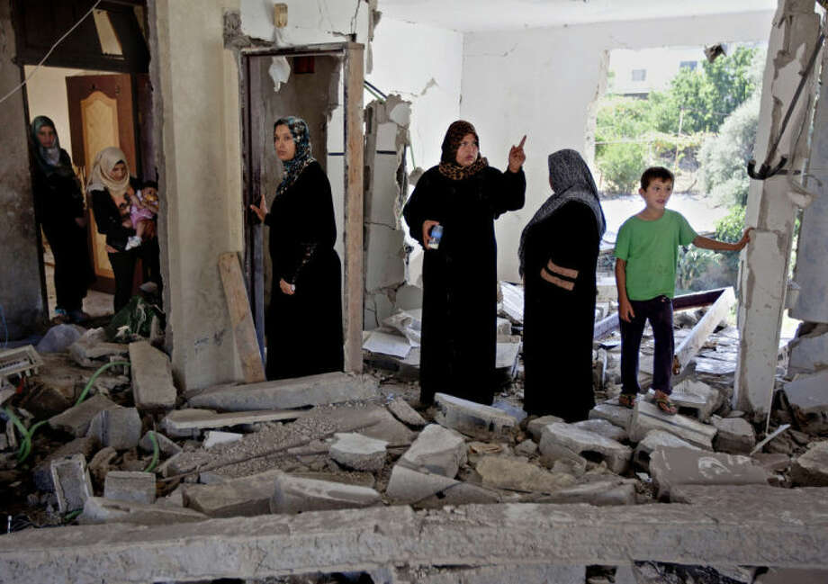 Palestinian women and children inspect the damaged family home of Ziad Awad in the town of Idna, 13 kilometers (8 miles) west of the West Bank city of Hebron, Wednesday, July 2, 2014. Israel demolished on Wednesday the home of Ziad Awad, who it accuses of having killed an Israeli police officer in April. The move marks a return to a policy abandoned by the military in 2005. Israel sees house demolitions as a deterrent to violence while critics charge it is a form of collective punishment. (AP Photo/Nasser Shiyoukhi)