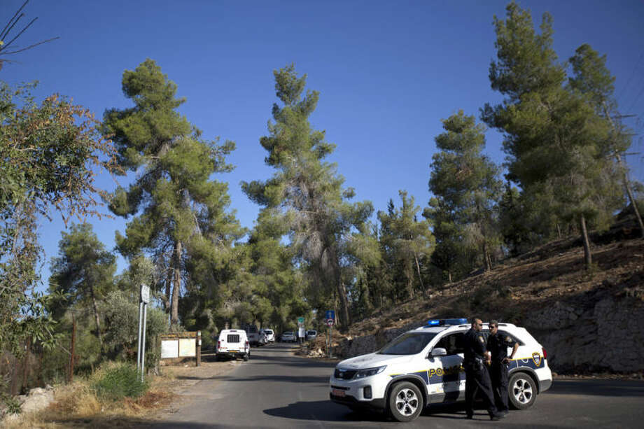 Israeli police officers block the entrance to a forest, where a body was found, in Jerusalem, Wednesday, July 2, 2014. Israeli police say Palestinians and Israeli forces have clashed following reports that an Arab teen was kidnapped and a body was found in a Jerusalem forest. Police spokesman Micky Rosenfeld said police received reports Wednesday that an Arab teen was forced into a car. A body was later found, but police have not yet established whether the two incidents are related. (AP Photo/Sebastian Scheiner)