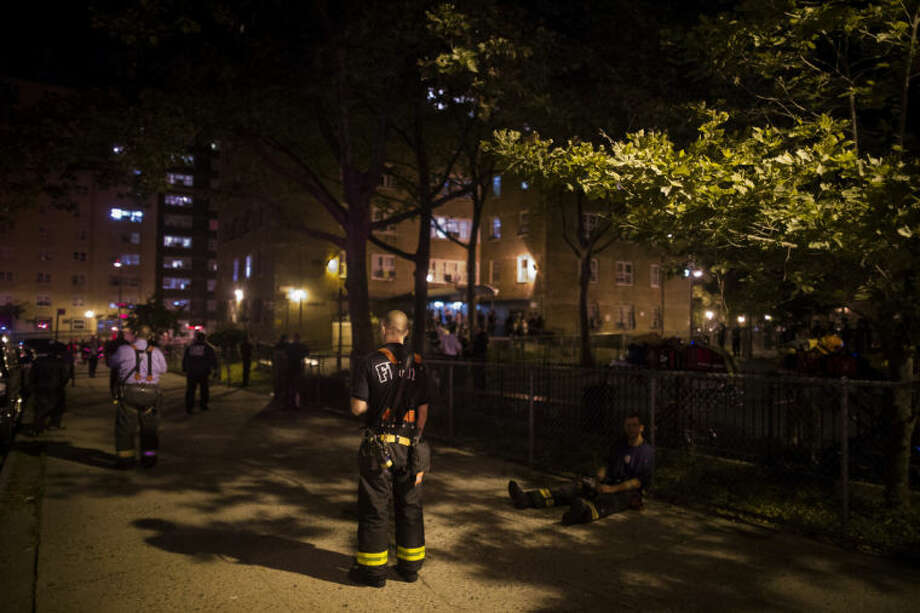 New York City firefighters work at the scene of a fire at public-housing high-rise building early Sunday, July 6, 2014, in the Brooklyn borough of New York. A fire department spokesman says Lt. Gordon Ambelas died at Woodhull Medical Center late Saturday night, July 5, after he was pulled from the building unconscious. (AP Photo/John Minchillo)
