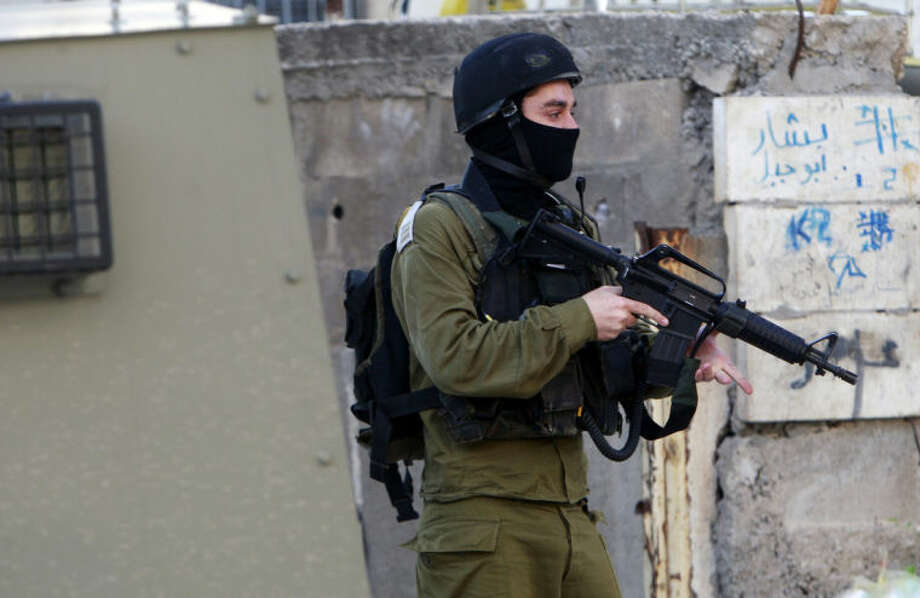 An Israeli army soldier takes a position during clashes with Palestinians in the early morning in the West Bank city of Jenin, Wednesday, July 2, 2014. Tensions have mounted between Israel and the Palestinians after the bodies of three Israeli teens were found in the West Bank more than two weeks after they went missing. (AP Photo/Mohammed Ballas)
