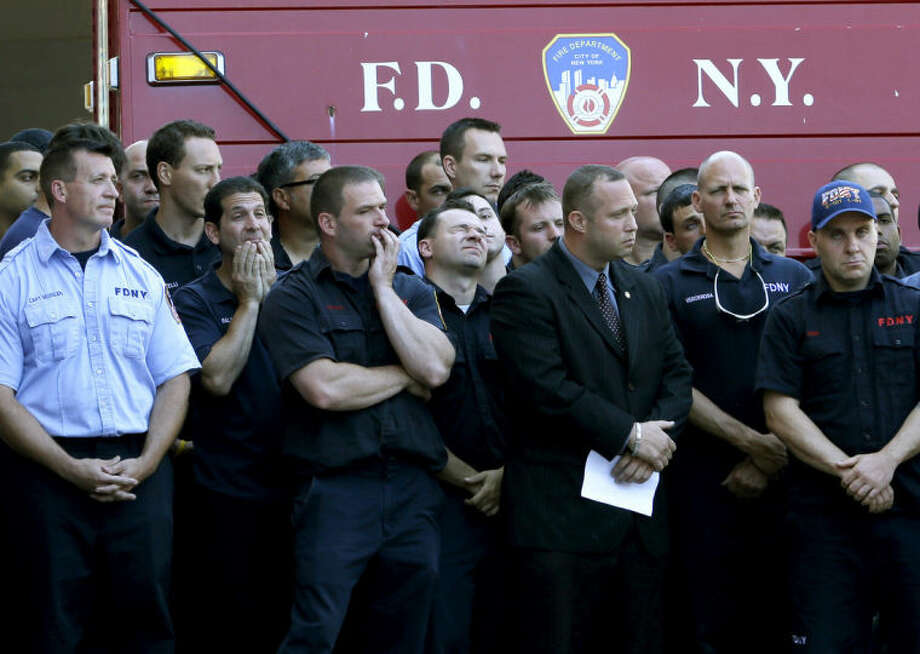 Firefighters solemnly watch as other firefighters hang bunting over the firehouse in honor of Lt. Gordon Ambelas in New York, Sunday, July 6, 2014. The Fire Department of New York is mourning the death of Ambelas, who became trapped while looking for victims in a public-housing high-rise blaze, the first to die in the line of duty in more than two years. Ambelas died Saturday after suffering multiple injuries while on the 19th floor of the 21-story building in the Williamsburg section of Brooklyn, officials said. (AP Photo/Seth Wenig)