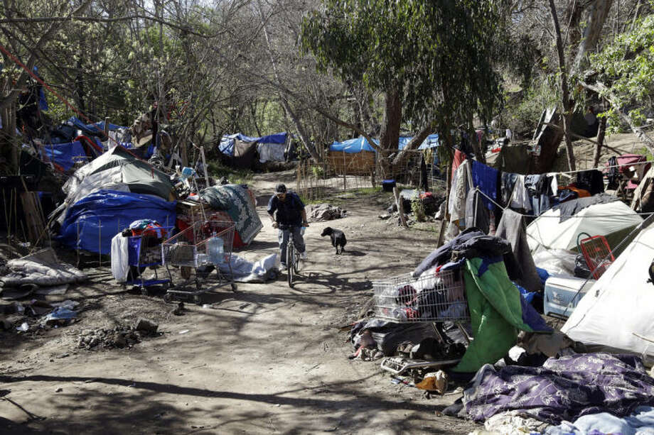 ADVANCE FOR USE SUNDAY, JULY 6, 2014, AND THEREAFTER- This March 11, 2014 photo shows tents set up along a pathway in the Jungle, a homeless encampment in San Jose, Calif. San Jose, the 10th largest city in the U.S., is at the heart of the Silicon Valley, a region leading the country for job growth, income, innovation and venture capital. Residents of the Jungle are well aware of the affluent world that lies just outside its borders. (AP Photo/Marcio Jose Sanchez)